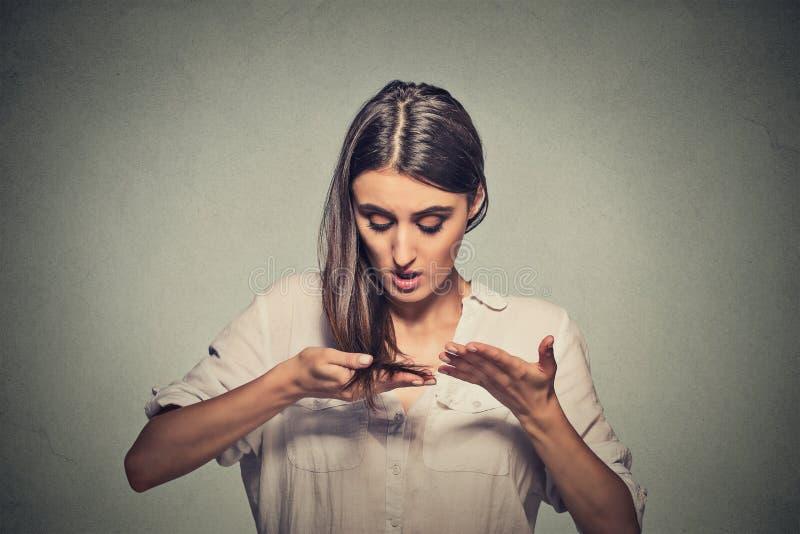 不快乐的沮丧的少妇使她惊奇是丢失的头发 免版税库存图片