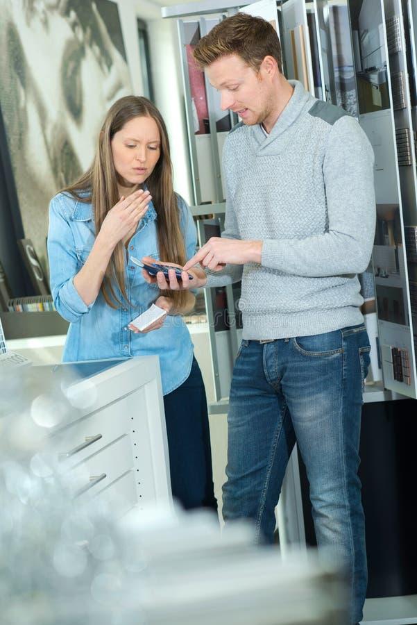 不快乐的男性客户争论价格与女性美发师 图库摄影