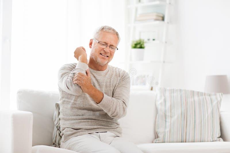 不快乐的老人遭受的手肘痛苦在家 免版税库存图片