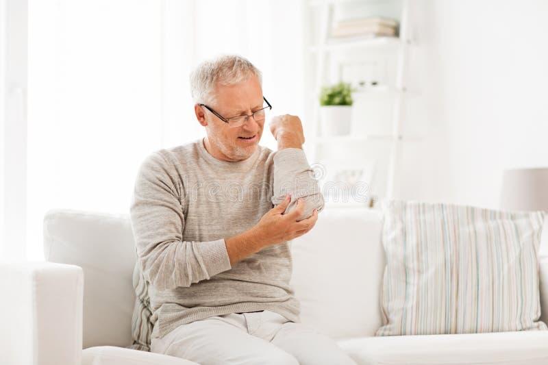 不快乐的老人遭受的手肘痛苦在家 库存照片