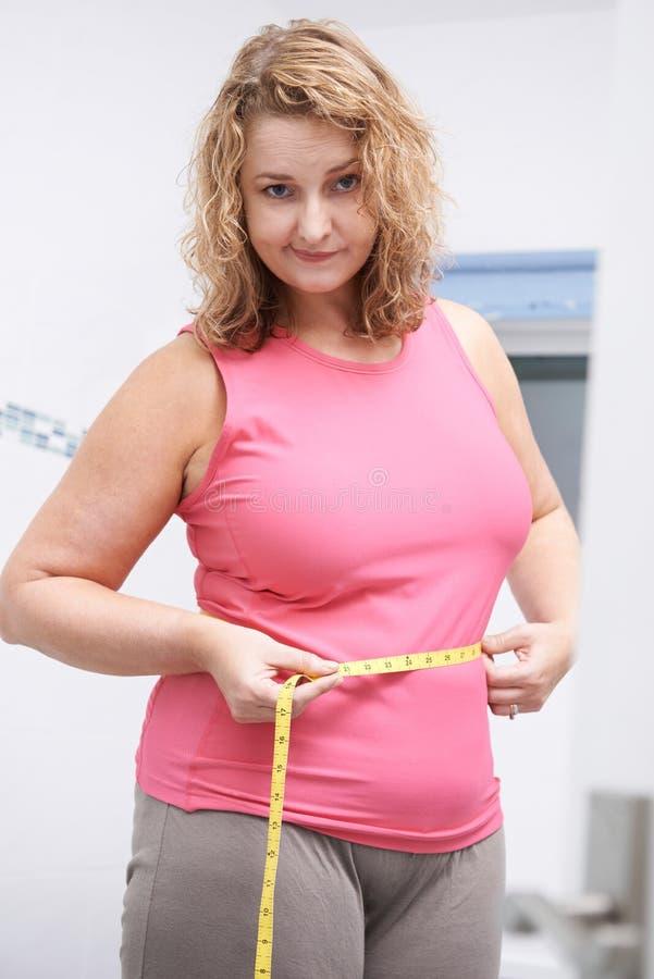 不快乐的超重妇女测量的腰部在卫生间里 免版税库存照片