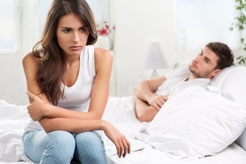 不快乐的年轻夫妇在卧室 免版税库存照片