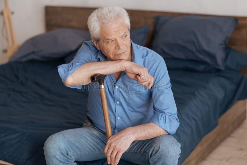 不快乐的年长人坐床 免版税库存图片