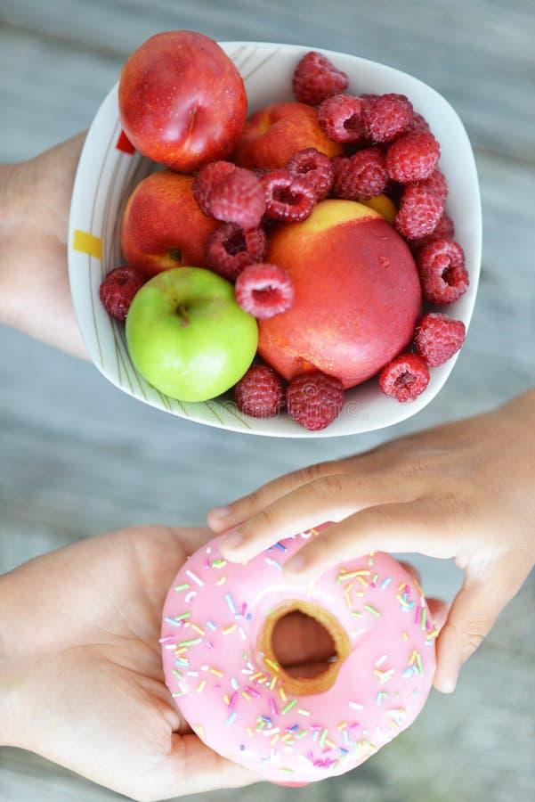 不抵抗的孩子诱惑选择一个有吸引力,但是不健康的多福饼而不是健康碗新鲜水果 库存图片