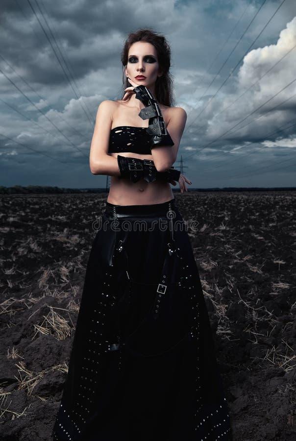 不拘形式的时尚:在黑皮革裙子和手套打扮的华美的亭亭玉立的年轻goth女孩 在领域的室外画象在定向塔附近 库存照片