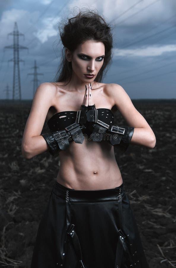 不拘形式的时尚:在黑皮革裙子和手套打扮的可爱的苗条年轻goth妇女 在近领域的室外画象 库存照片