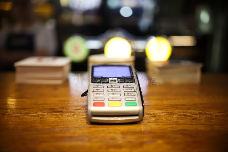 不接触的付款的一个终端与智能手机在桌上 免版税库存图片