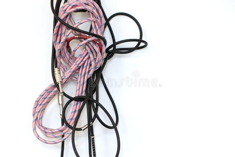 不整洁乐器缆绳 被缠结的吉他带领垂悬在墙壁上 免版税库存照片