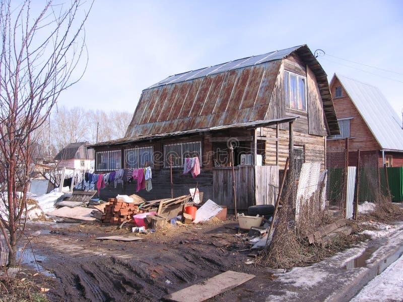 不整洁的老木房子在假日村庄垂悬与洗衣店在unharvested春天的庭院里在西伯利亚 库存图片