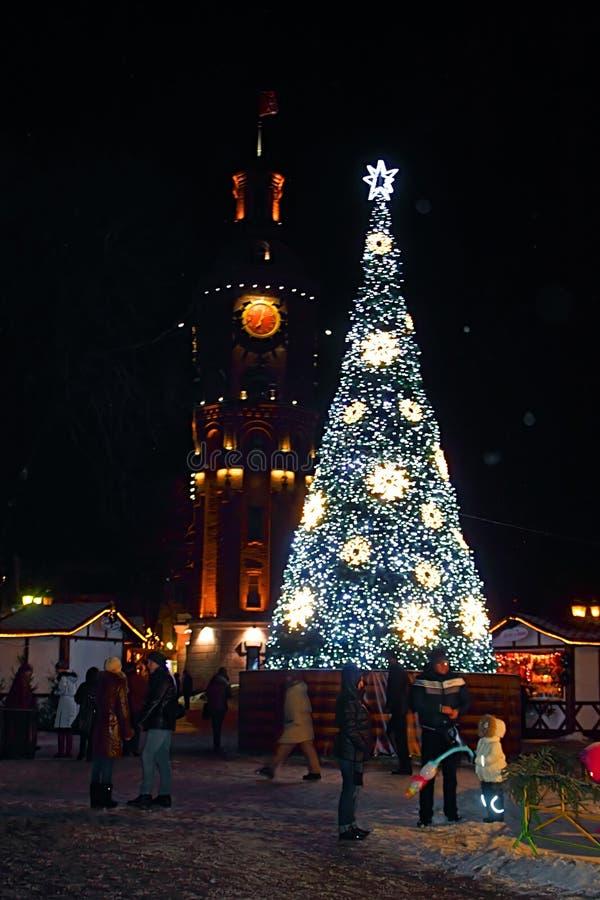 不明身份的人民庆祝除夕靠近与时钟的老了望塔和Chistmas树在晚上,文尼察州,乌克兰 库存图片