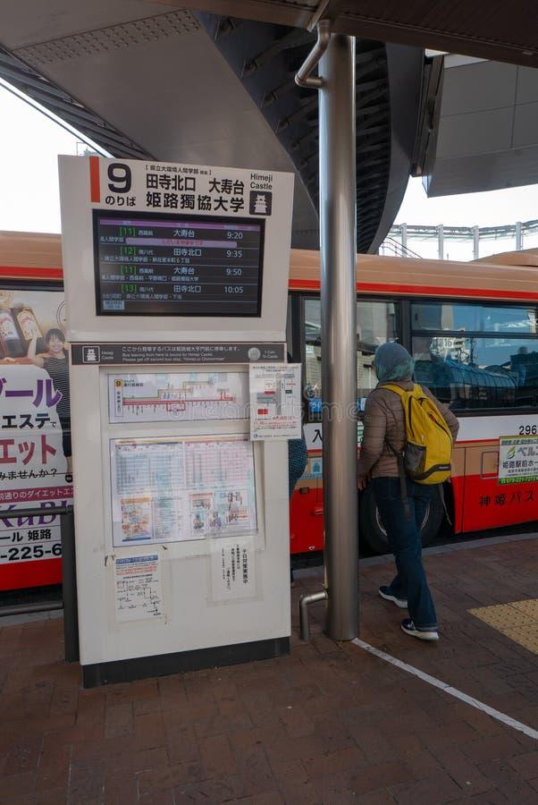 不明身份的回教妇女在姬路公交车站,日本等待公共汽车 库存照片