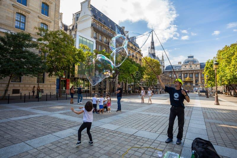 不明身份的街道艺术家在巴黎,法国吹巨大的五颜六色的肥皂泡 库存图片