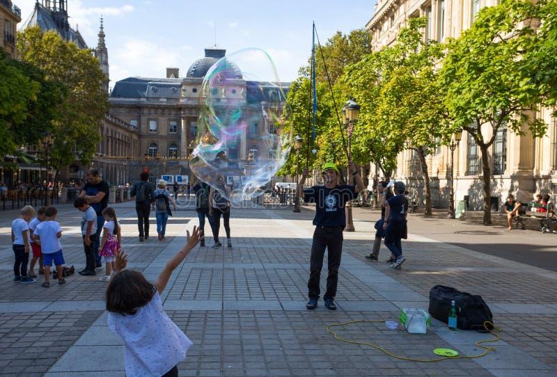 不明身份的街道艺术家在巴黎2018年9月9日吹巨大的五颜六色的肥皂泡 免版税库存照片