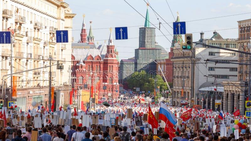 不朽的军团队伍在胜利天-前进沿Tverskaya街的上千群众往有旗子的红场 免版税库存图片