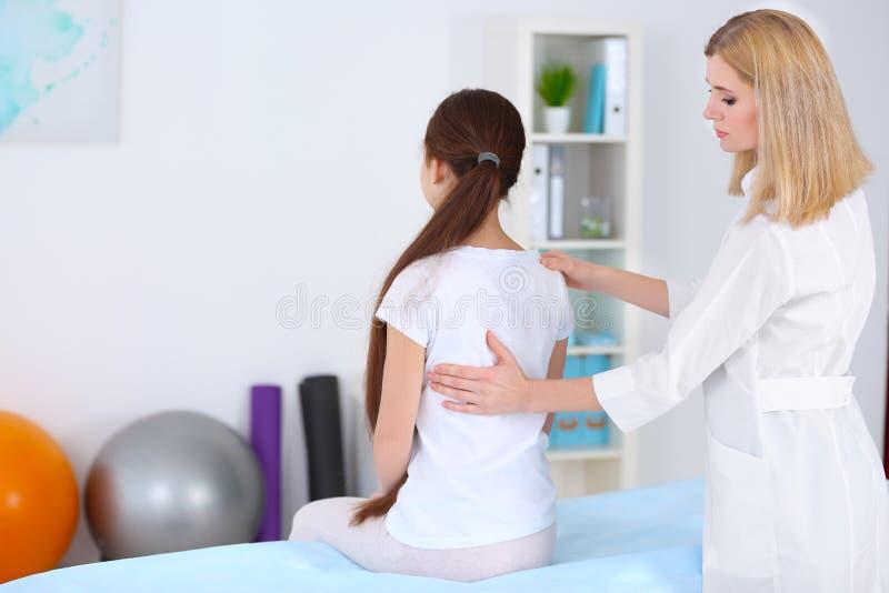 不正确姿势概念 审查和改正女孩` s后面的生理治疗师 免版税图库摄影