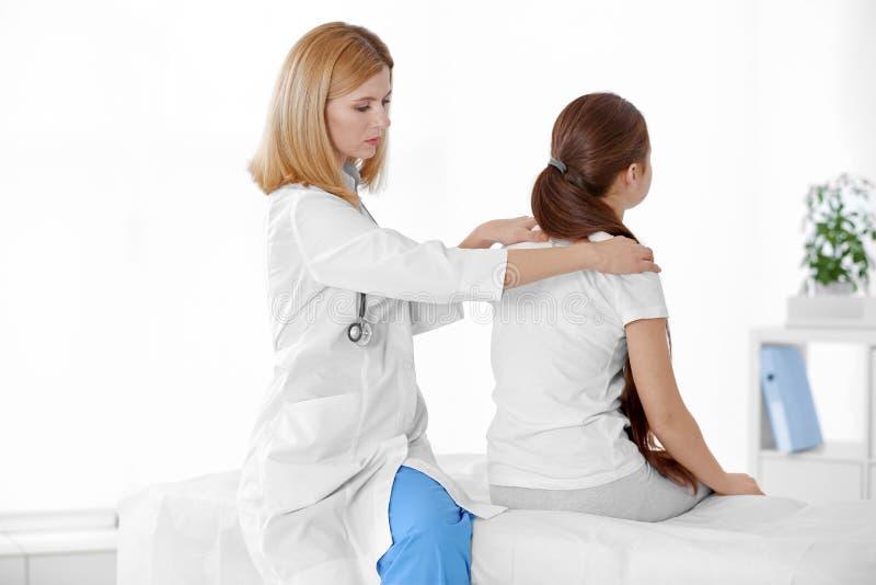不正确姿势概念 审查和改正女孩` s后面的生理治疗师 免版税库存图片
