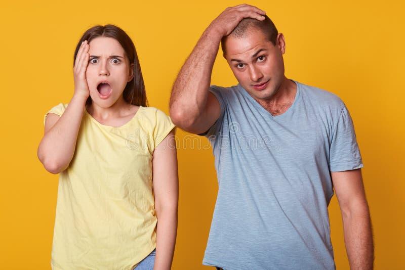不满意的夫妇室内演播室射击,有问题,与宽张的嘴的妇女身分,接触面孔用手,看 库存照片