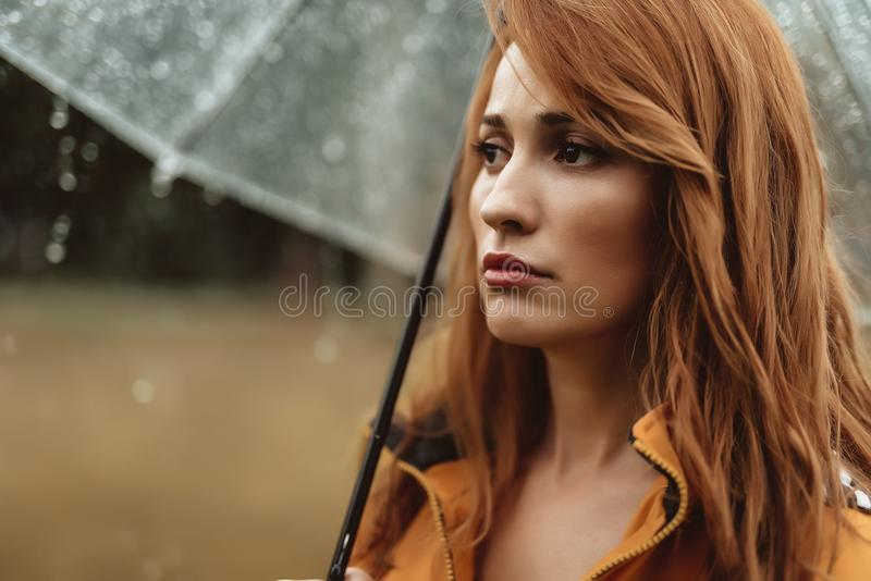 不满意的妇女常设外部在雨中 免版税库存照片