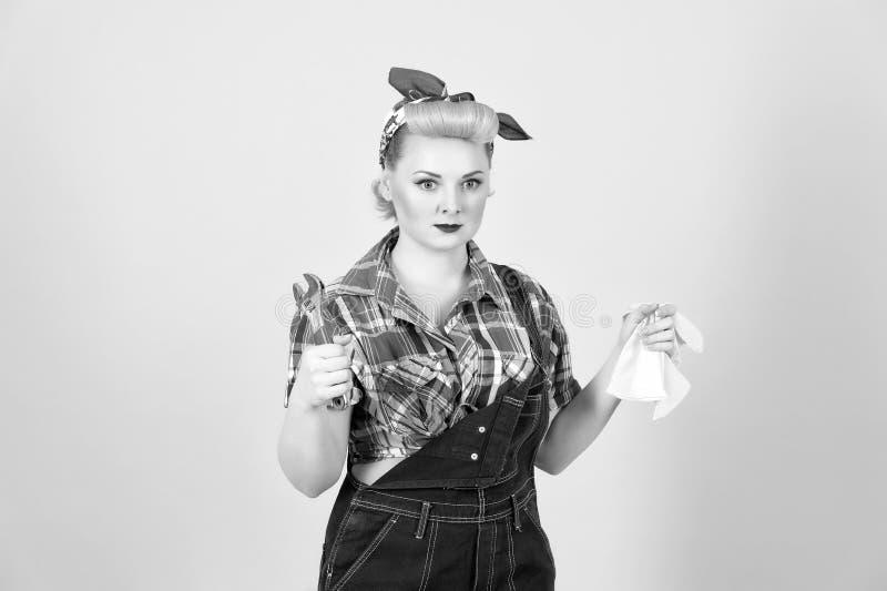 不满意的画报样式的年轻坚强的女孩拿着板钳 免版税库存图片
