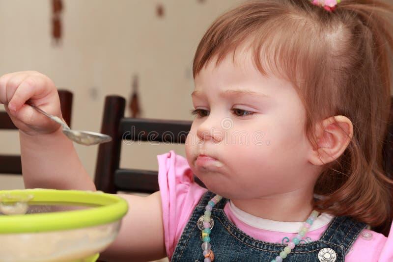 不满的吃表面女孩粥 免版税库存照片