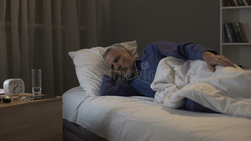 不耐烦地等待早晨的领抚恤金者在晚上来,遭受的失眠 免版税库存图片