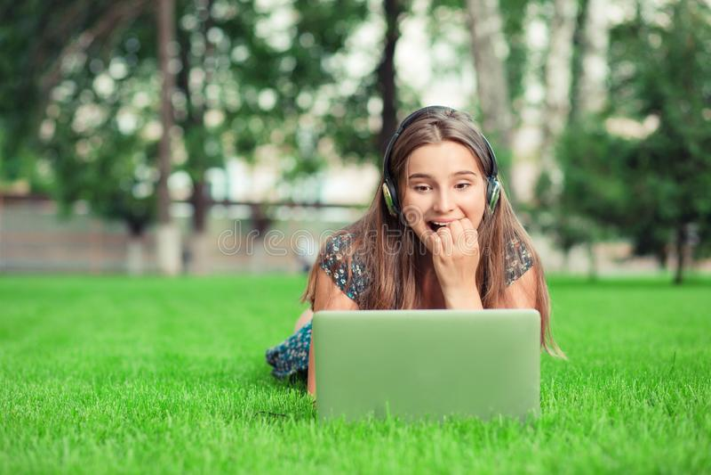 不耐烦的愉快的女孩束手无策,当她等待网电话或在膝上型计算机时的答复对她的闲谈或sms 免版税库存照片