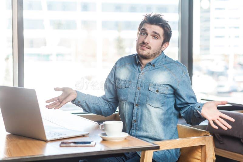 不肯定!迷茫的英俊的有胡子的年轻自由职业者画象蓝色牛仔裤衬衣的在咖啡馆坐并且研究膝上型计算机 免版税库存图片