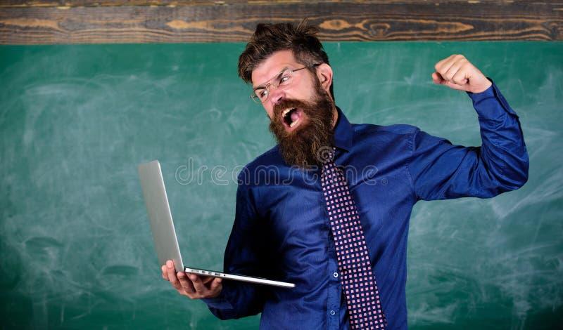 不能习惯现代技术 技术使他惊奇 有现代膝上型计算机黑板的老师有胡子的人 免版税图库摄影