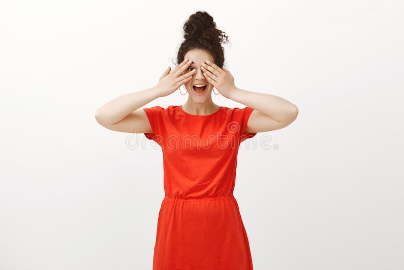 不能等待看惊奇 时髦的红色礼服的正面激动的女朋友,咧嘴和盖注视与棕榈 免版税库存照片