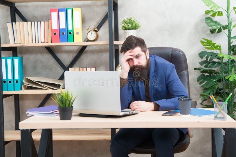 不能记住他的密码 人有胡子的上司坐办公室膝上型计算机 在网上解决业务问题的经理 ?? 免版税库存图片
