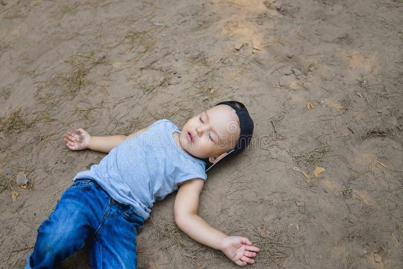 不自觉的小男孩放置在地面假装的睡眠或 图库摄影