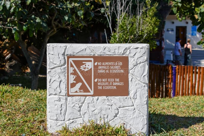 不要喂养野生生物,它损坏生态系 签到英语和西班牙语在密林背景前面 图库摄影