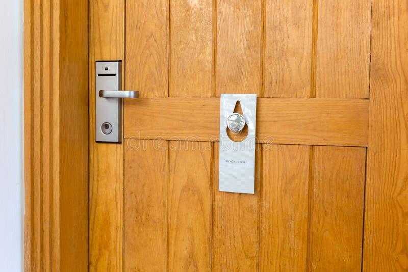 不要干扰在酒店房间的闭合的木门的标志 图库摄影