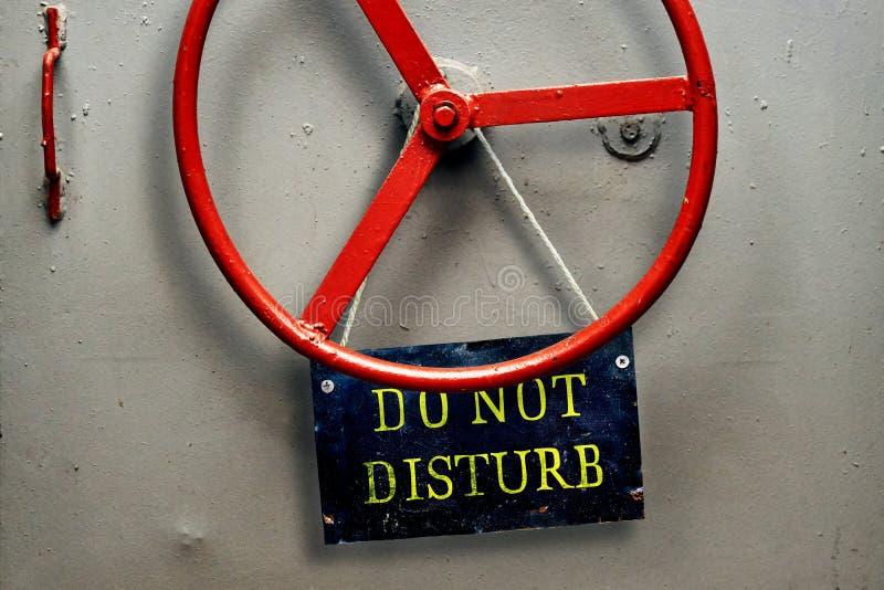 不要干扰垂悬在一个密封防空洞装甲的门的警报信号板材 免版税库存照片