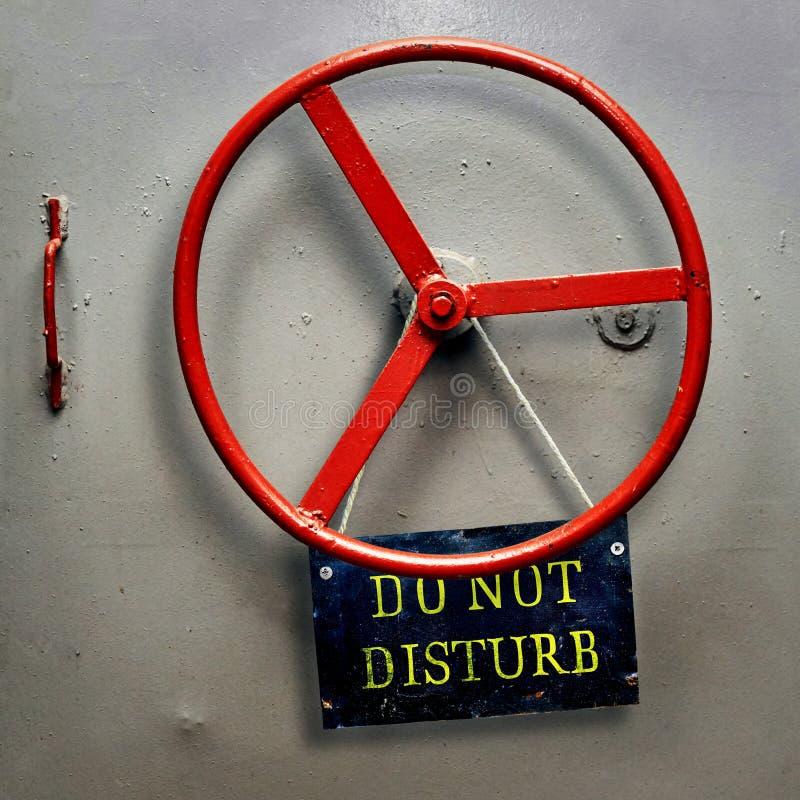 不要干扰垂悬在一个密封防空洞装甲的门的警报信号板材 库存照片