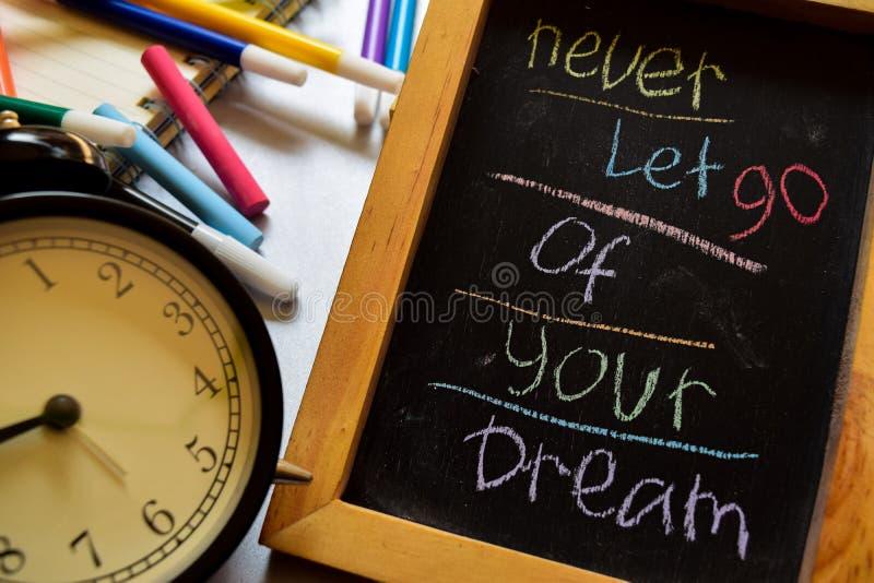 不要放弃您的在词组五颜六色手写的梦想在黑板、闹钟以刺激和教育概念 图库摄影