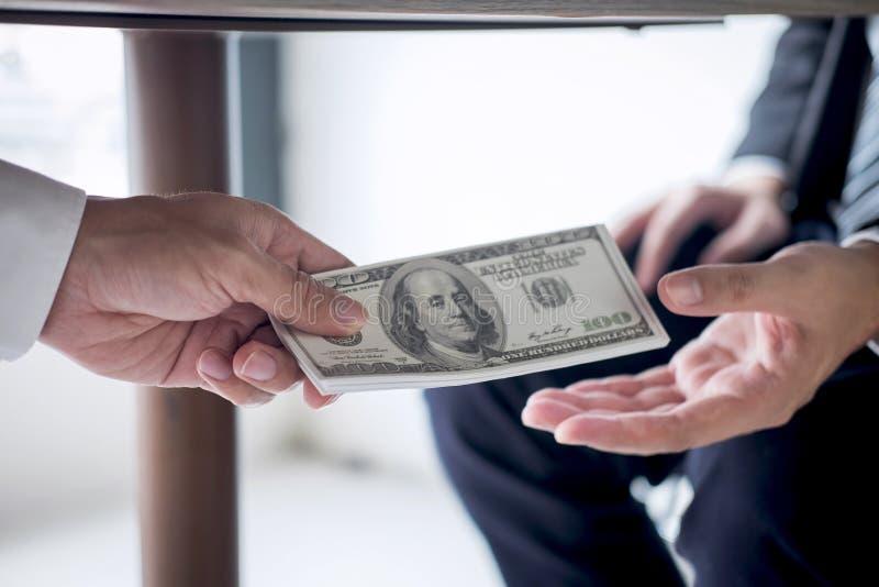 不诚实欺诈在企业非法金钱,商人收到贿款金钱在桌下给商人给的成功 库存照片