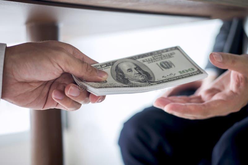 不诚实欺诈在企业非法金钱,商人收到贿款金钱在桌下给商人给的成功 库存图片