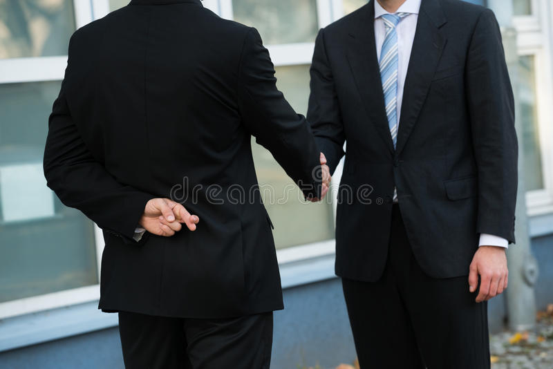 不诚实的商人与伙伴握手 免版税库存图片