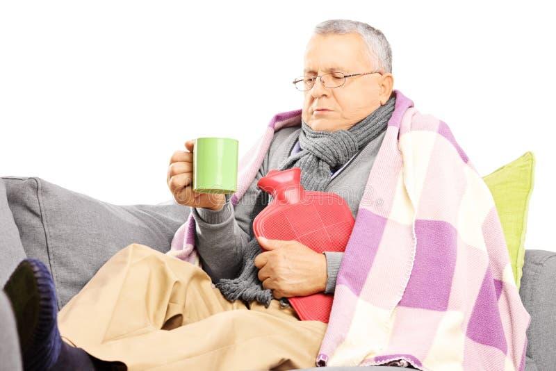 不适的中部用毯子喝盖的沙发的年迈的人热 免版税库存照片