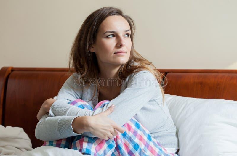 不适的妇女在床上早晨 图库摄影