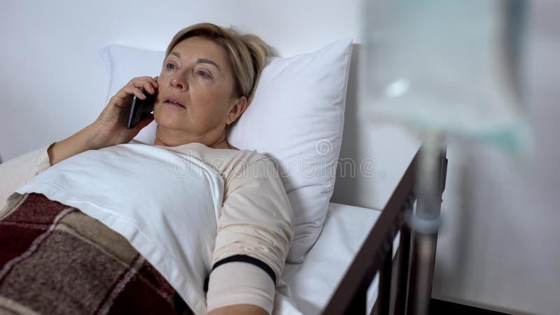 不适的妇女谈话在有下落柜台的智能手机,在医院病床上,健康 免版税库存图片