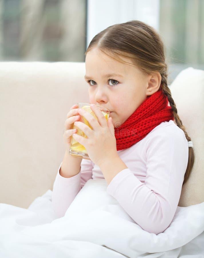 不适的小女孩喝着维生素鸡尾酒 图库摄影