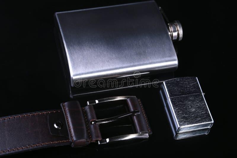 不锈的熟悉内情的在镜子黑色背景和豪华传送带隔绝的烧瓶、打火机 免版税库存照片