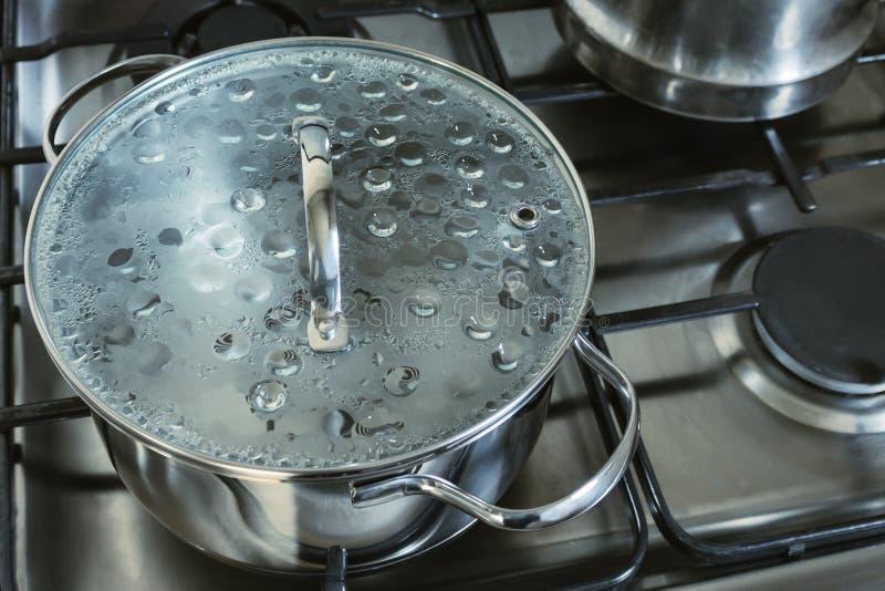 不锈钢平底深锅 有玻璃盒盖的罐有开水的在煤气炉 免版税库存图片
