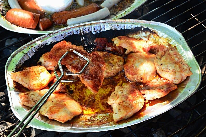 不锈钢握在alluminium板材、香肠和软制乳酪板材上的烤肉钳子嘎吱咬嚼的烤鸡胸脯在backg 库存照片