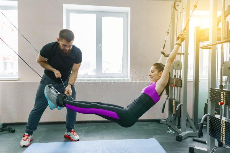 不随意运动技术,运动疗法,健康生活方式 做与个人辅导员使用的年轻女人修复锻炼 图库摄影