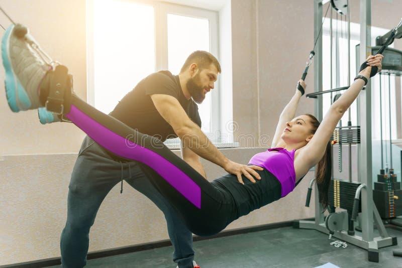 不随意运动技术,运动疗法,健康生活方式 做与个人辅导员使用的年轻女人修复锻炼 库存照片