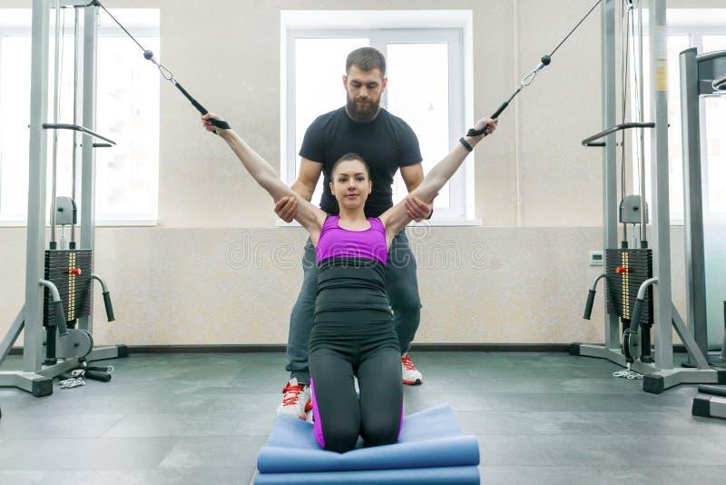 不随意运动技术,运动疗法,健康生活方式 做与个人辅导员使用的年轻女人修复锻炼 免版税库存图片