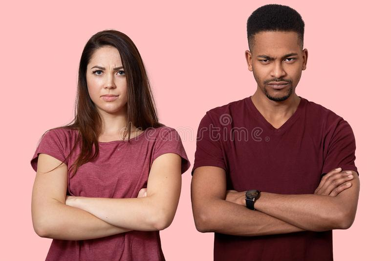 不高兴的生气的人种间朋友水平的射击保留胳膊重叠的胸口,有坏关系,穿便服 库存照片